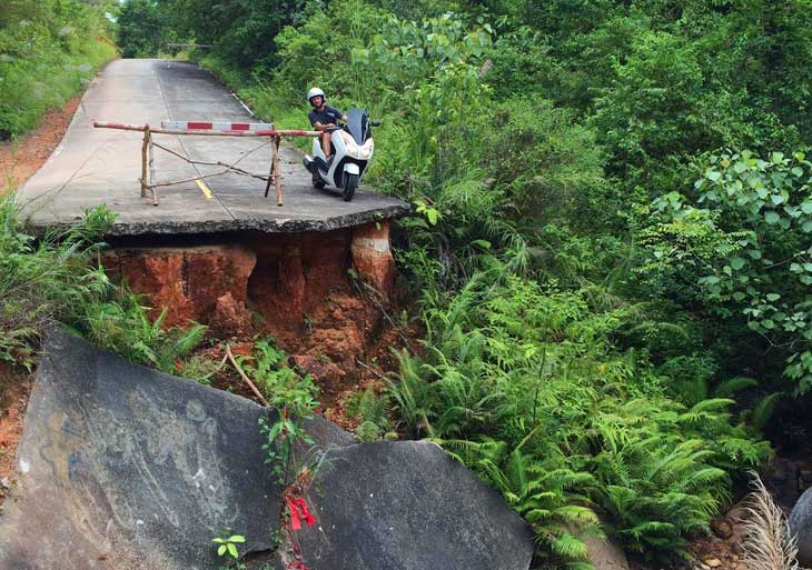 Motorbike driver at the edge of broken bridge in Thailand