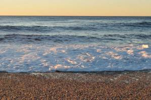 Stunning beach at sunset with foamy waves covering the beach and a beautiful horizon where the sea meets the sky