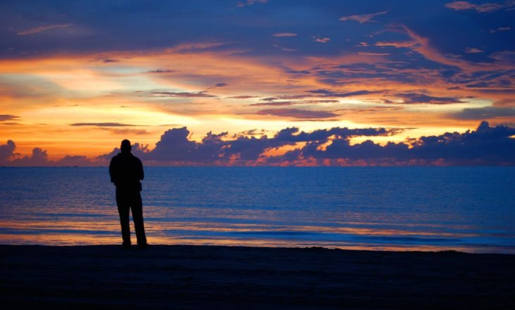 Silhouette of a man enjoying a solemn moment looking at a stunning sunset at the beach.