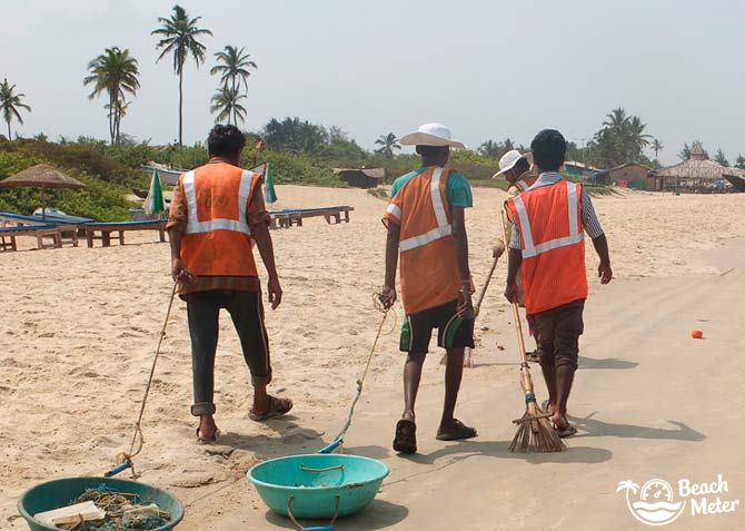 Indian beach cleaners in Goa walking along the beach while tidying and picking up garbage.