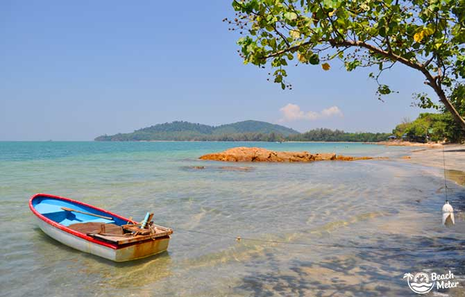 Rowing boat lying in clear water near the shore of Koh Chang Noi Island in Thailand