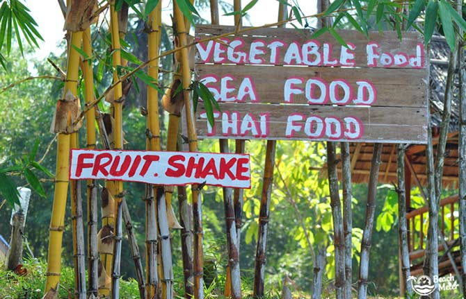 Wooden signs on a tropical island in Thailand saying fruit shake, vegetable food, seafood, and Thai food.