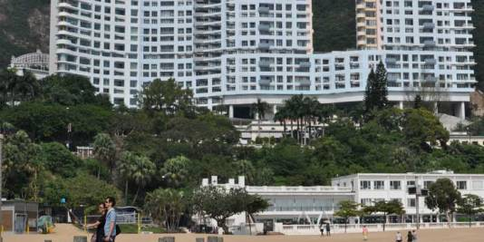 Tourist couple taking a selfie at Repulse Bay with The Repulse Bay building in the background