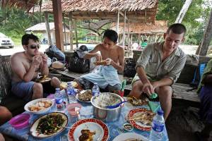 Two tourists and a local man eating an Indonesian lunch of chicken, fish, rice, and vegetables with their fingers at Asi Walo Beach, Nias Island, Indonesia