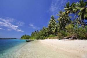 Beautiful beach with small boat and clear water on Makora Island, north of Nias Island, Indonesia