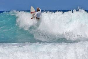 Surfer riding the rough foaming waters at Pasir Merah Beach, North-West Nias, Indonesoa