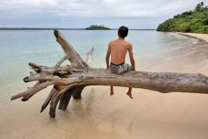 Man sitting on a tree with his feet hanging over the water, Panjang Island off the north coast of Nias Island, Indonesia