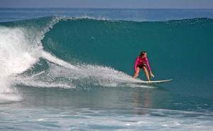 Surfer Girl riding a huge wave at Afulu Beach in Nias Island, Indonesia