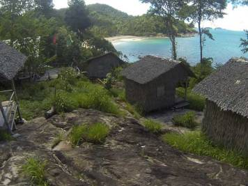Simple and basic bamboo and straw bungalows on a hill overlooking the beautiful bay at Wai Chaek Beach, Koh Chang, Thailand.