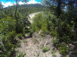 Steep dirt path leading to a tropical beach on Koh Chang island in Thailand.