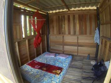 Interior of simple bungalow accommodation in Koh Chang, Thailand - mattress on the floor, mosquito net, and kerosene lamp