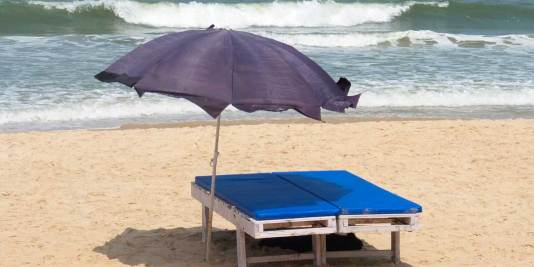 Black dog lying in the shade under a beach bed and sun umbrella with the sea in the background