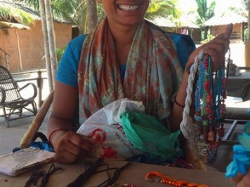 Beach seller selling homemade bracelets, anklets, and necklaces