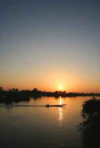 The sun sets over the Mekong River in Laos with a silhouette of a longtail boat.
