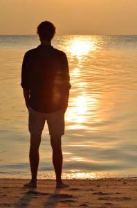 Man viewing mesmerizing sunset at the beach in Selingan Island, Borneo.