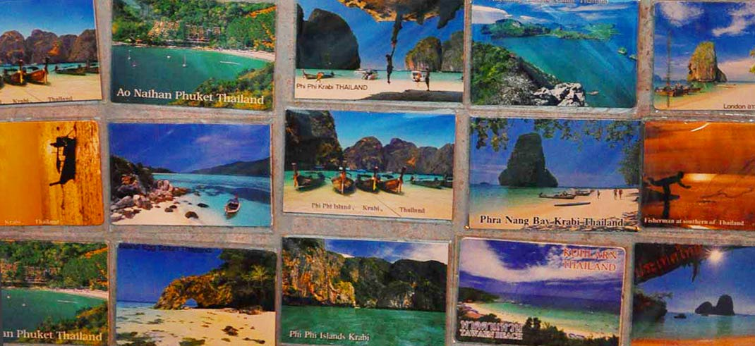 Photo of postcards of Thai beaches including Phi Phi Islands, Phuket, Krabi, Phra Nang Bay, and Ao Nathan.