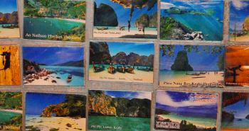 Photo of postcards of Thai beaches including Phi Phi Islands, Phuket, Krabi, Phra Nang Bay, and Ao Nathan.