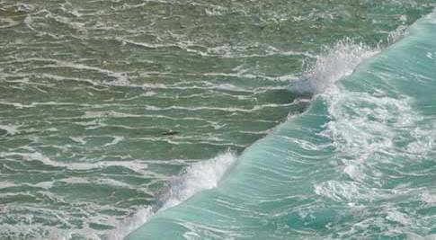 A wave coming in on the shoreline of the Big Sur coast