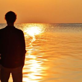 Man overlooking a magnificent sunset over the Sulu Sea in Malaysian, Borneo. Photo by Beachmeter.com.