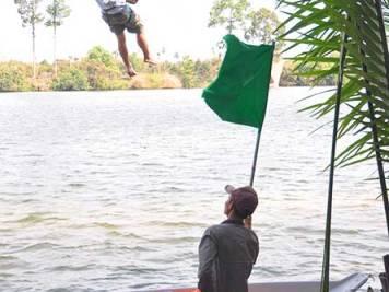 Man ziplining over the Kampot River in Cambodia