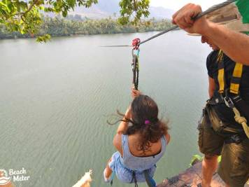 Girl on zipline over Kampot River at Kampot Zipline River Park.