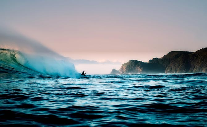 Surfer riding wave at Piha New Zealand
