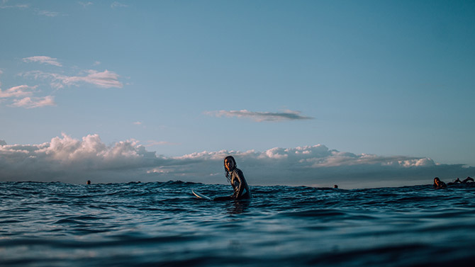new zealand surfer sitting on surfboard waiting for a wave