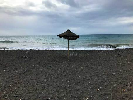 lonely parasol on black sand beach