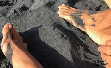 tanned feet in black volcanic sand