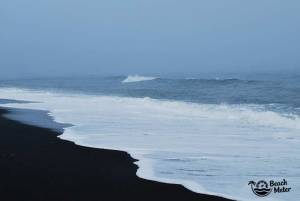 black sand beach and white foamy water on a misty day