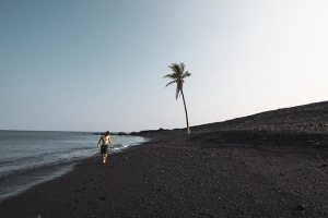 Man on black sand beach in Hawaii