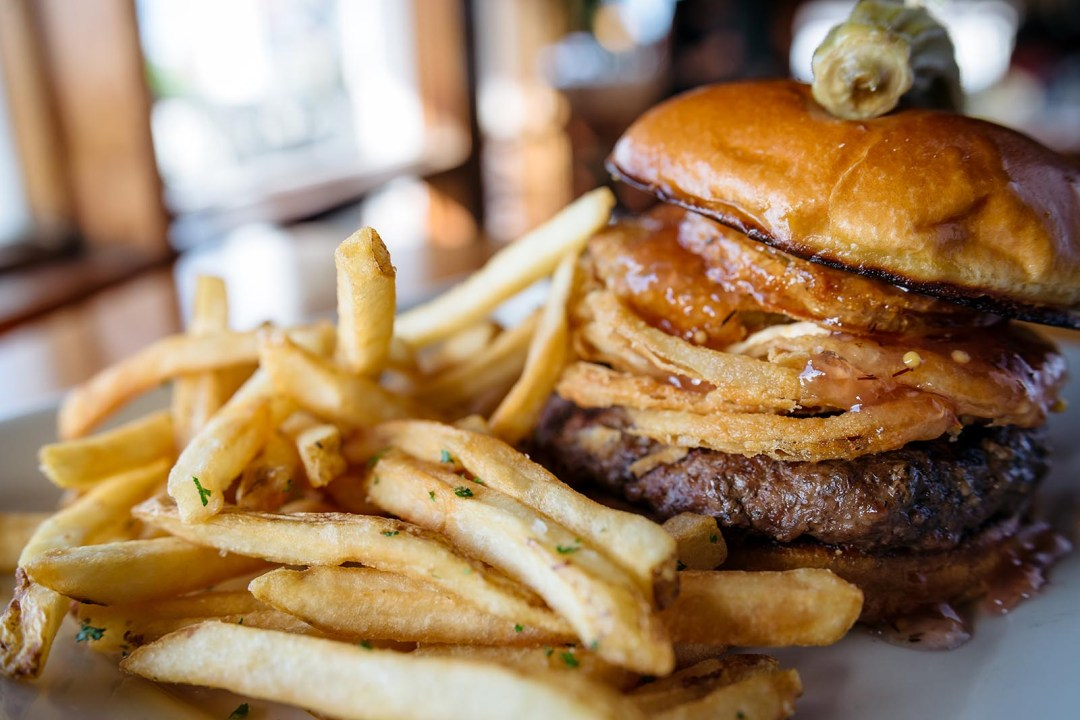 Southern Bistro Burger: 8 oz. grass fed burger with fried green tomatoes, bacon jam, fried tabasco onions, and pimento cheese spread on brioche roll. Served with fries.
