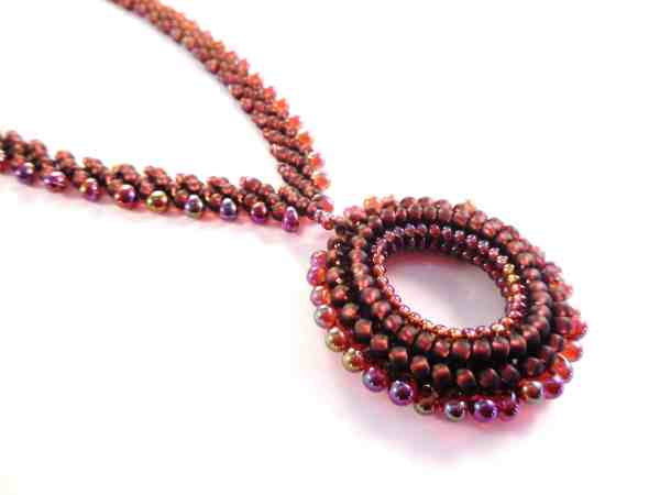 The beading pattern for the Holiday Wreath Necklace uses St. Petersburg Stitch, while the pendant is made using Tubular Herringbone Stitch.