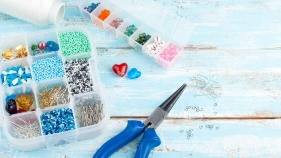 Flat lay of beading supplies including beads, findings and pliers.