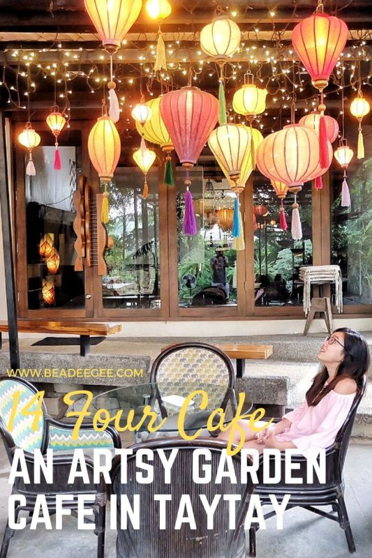 a girl sitting down looking at the colorful lantern on top of her in 14 Four Cafe