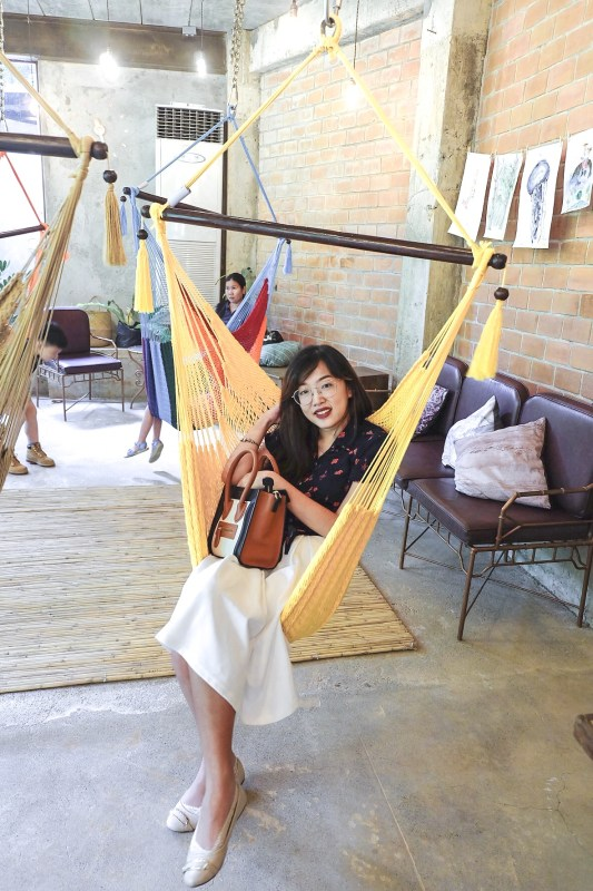a girl in a yellow hammock in burrow cafe antipolo