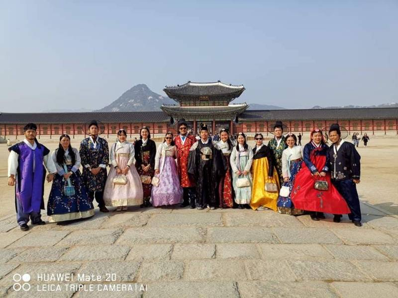 A big family wearing Korean hanbok in front of Gyeongbokgung palace in Seoul