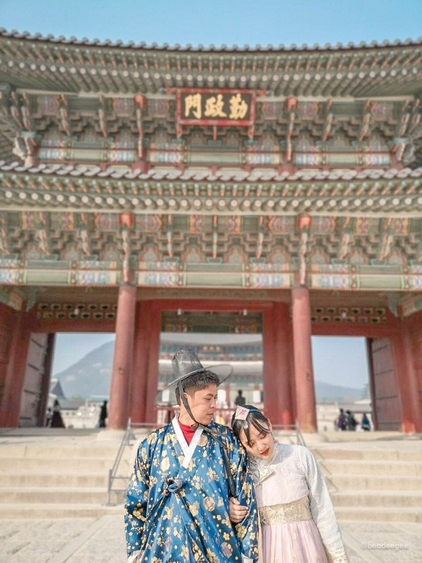 A couple wearing korean hanbok in front of Gyeongbokgung Palace in Seoul