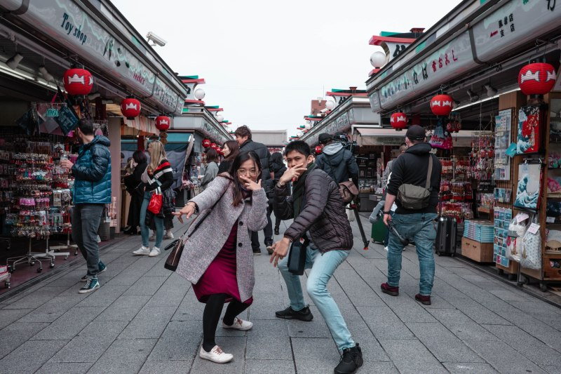 a couple doing wacky pose along the stores to sensoji temple