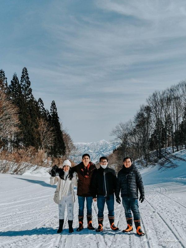 four people in a snow background when yiu take the snowmobile sleigh tour in gala yuzawa