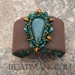 Bead embroidered cuff with moss agate cabochon, raw emerald, faceted tiger's eye and glass seed beads.