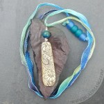 Engraved bone pendant with henna design.