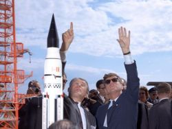 Werner von Braun (left) and President Kennedy at Cape Canaveral. At left an early model of a Saturn V rocket designed by von Braun.
