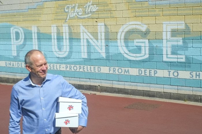 image of Briggs shoes owner Tom Powney in front of one of Morecambes seafront wall murals