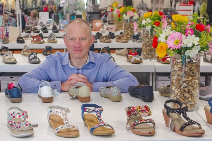 image of Briggs shoes owner Tom Powney and son in the Briggs Shoes shop amongst the shoe displays