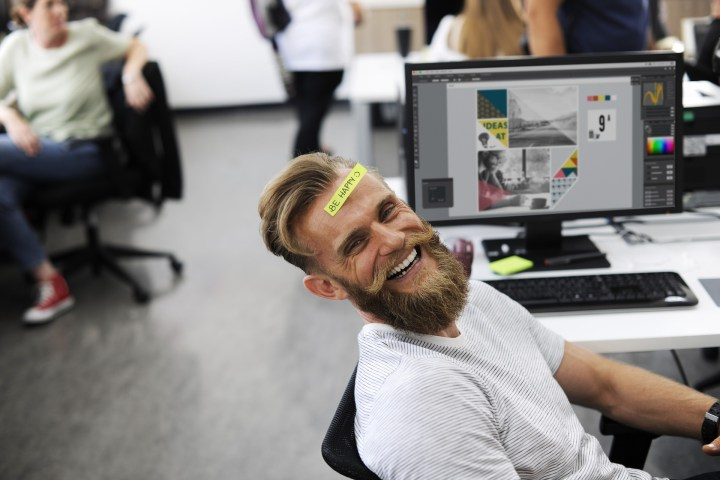 A guy sitting at his work desk smiling.