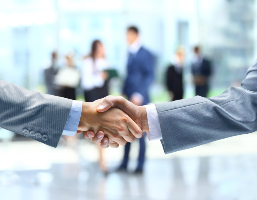 Two people wearing business suit shaking hands