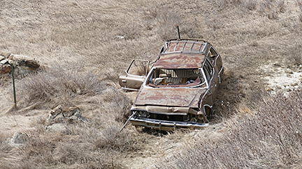 A crashed station wagon is left to rot in  ditch next to Highway 8.