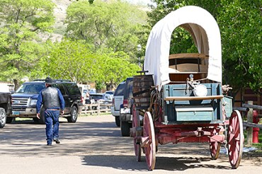 A cowboy walks past a covered wagon.