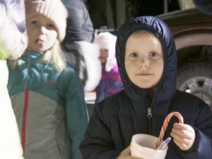 Kids bundled up, enjoying hot chocolate and candy cane.